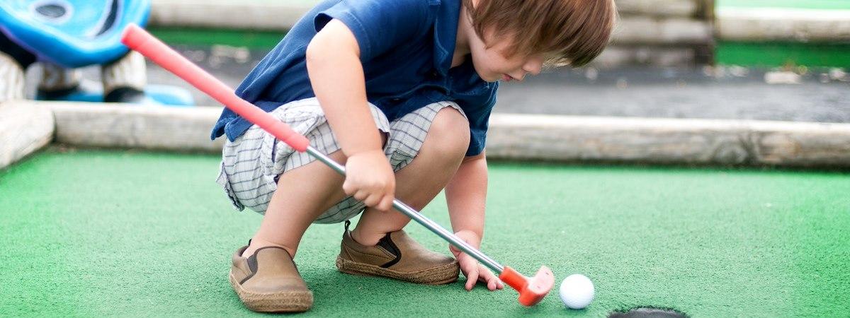 child playing minigolf